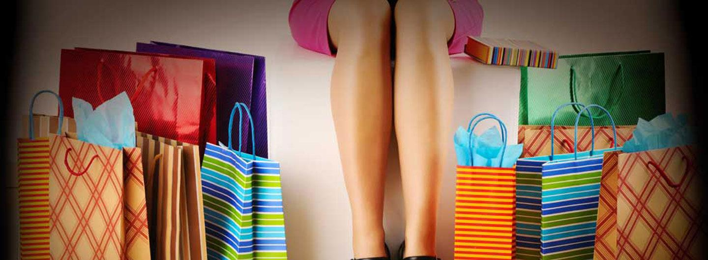 A lady's legs next to shopping bags
