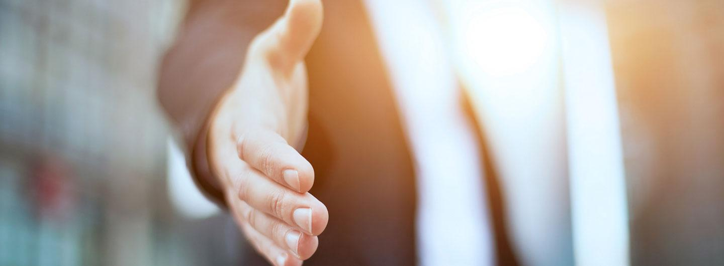 A man trying to shake someones hand to agree upon incentives