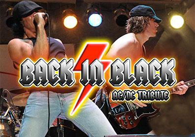 Band members on stage performing in AC/DC inspired costumes with band name graphic