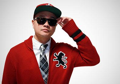 DJ wearing sunglasses, cap, tie and red sweater