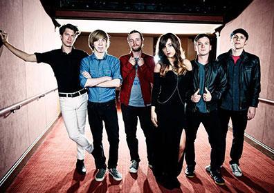 Band members posing in dark hallway