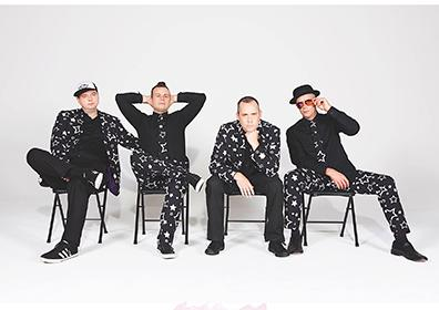 Band members posing in star-studded suits