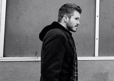 Artist posing in profile against walkk in black and white