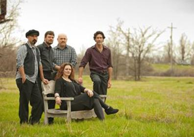 Band members posing in large pasture