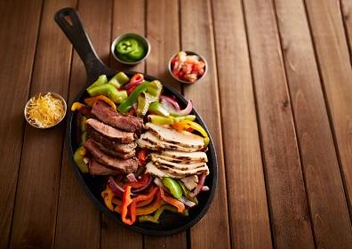 of chicken and steak fajitas with cheese, peppers and other trimmings on a wooden table