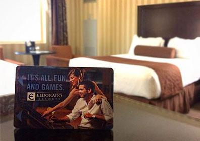 Hotel room key with king-size bed in background