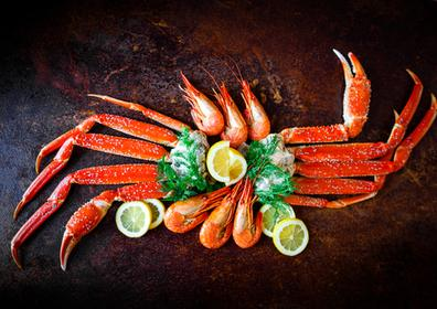 of boiled crab legs and shrimp aesthetically placed in a circle on a wooden platform