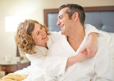 Couple in bathrobes hugging on hotel room bed