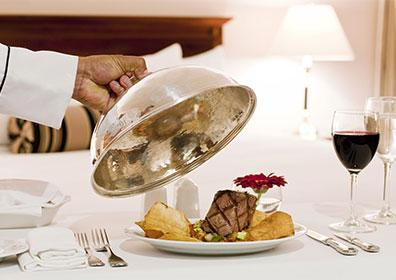 Server pulling cloche off of tray of food on bed