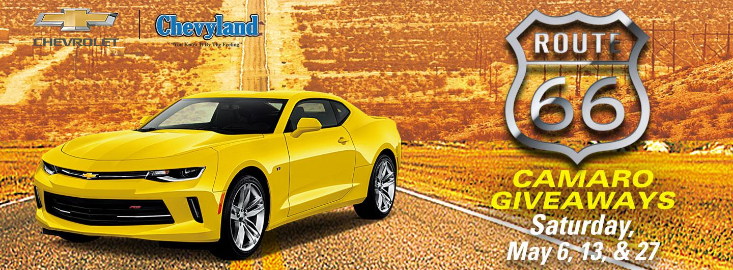 Yellow Camaro on dessert highway with event text and dealership logo