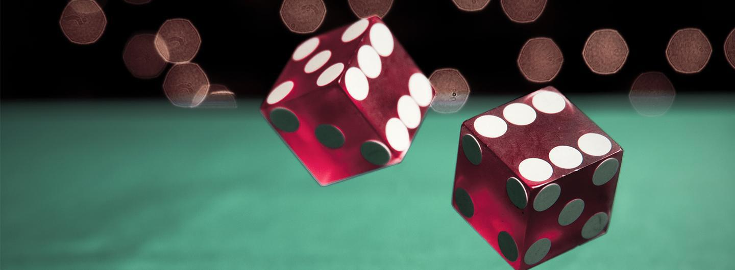 Red dice rolling on felt-top table