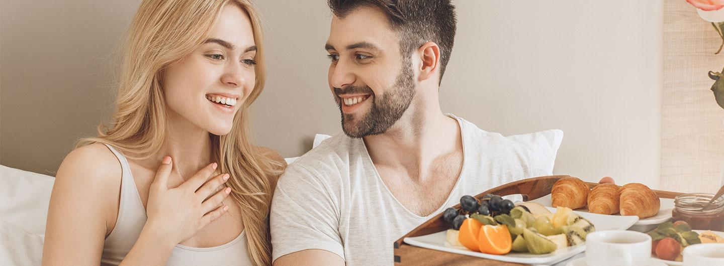 Couple being handed breakfast tray in bed