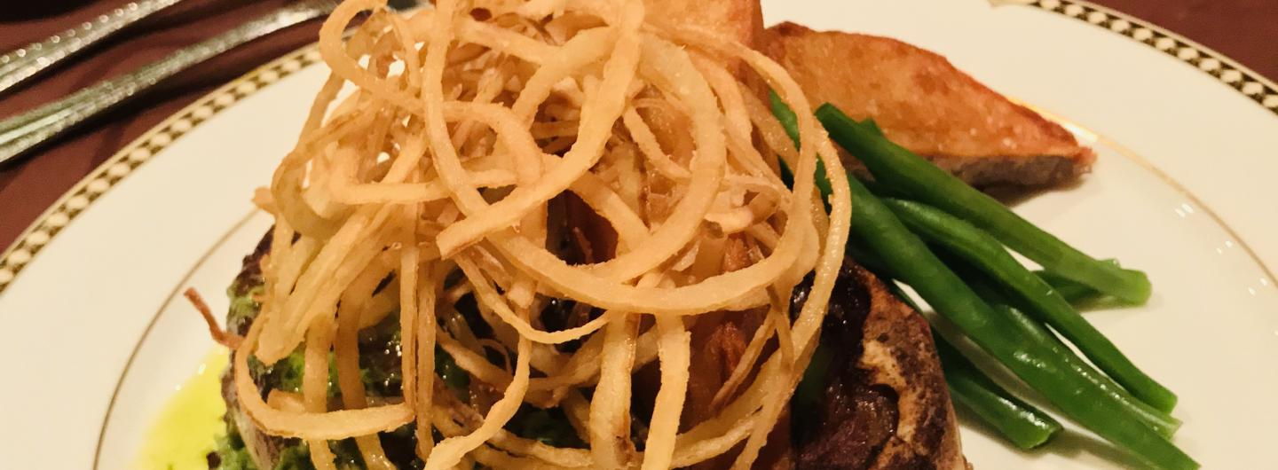 Charbroiled Kansas City strip lightly rubbed with coffee topped with tobacco onions served with a side of herbed butter steak fries and hericot verts