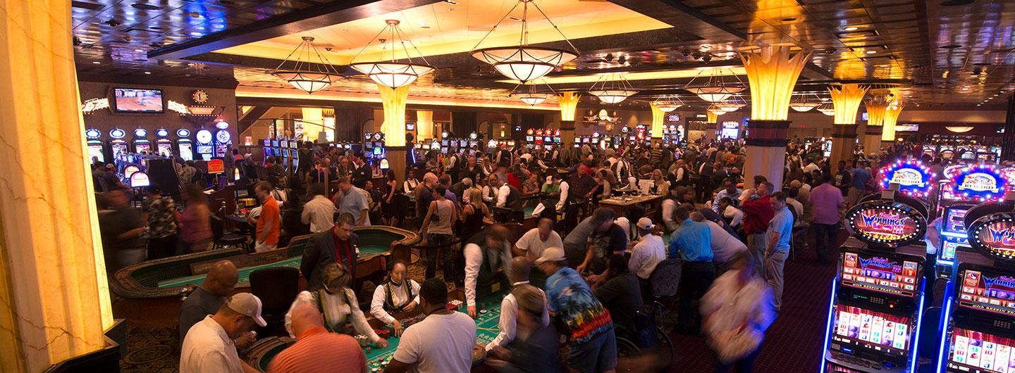 Busy casino floor with table games and slot machines.