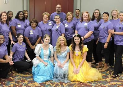 people in purple shirts with 3 disney princesses