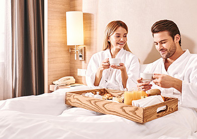 Two people enjoying breakfast in bed