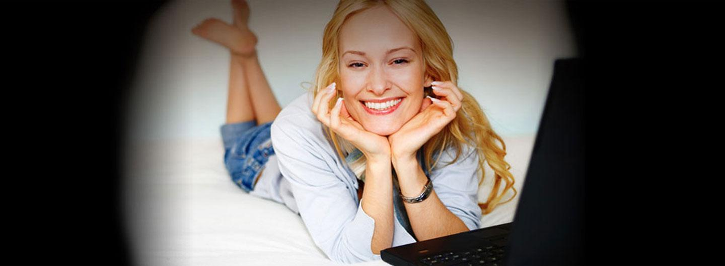 A lady smiling next to her computer for wireless internet access