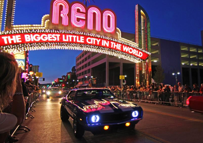 Hot Rod Cars Driving Under the Reno Arch at night