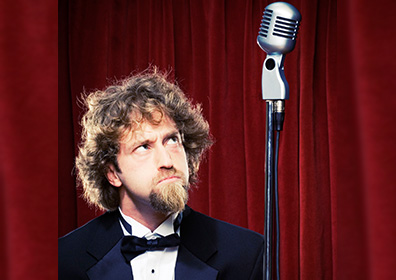 Josh Blue looking up towards Mic with red curtains in background