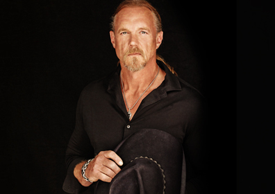 Trace Adkins dressed in black with black cowboy hat held in front of his chest.