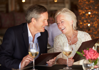 Senior Couple Smiling and Holding Menus in a Dinner Restaurant