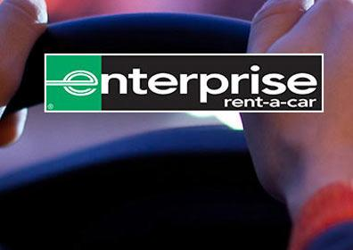 A person with their hands on a steering wheel with Enterprise's logo.