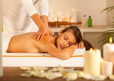 woman getting a massage surrounded by candles