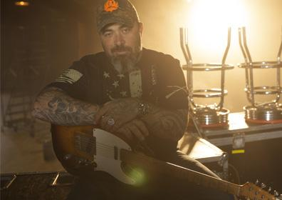 Aaron Lewis with sitting with a guitar
