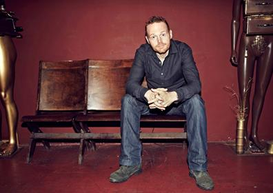 Bill Burr sitting on Wood Bench against Red Wall
