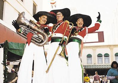 3 Men on Stilts dressed like Italians with Large instruments