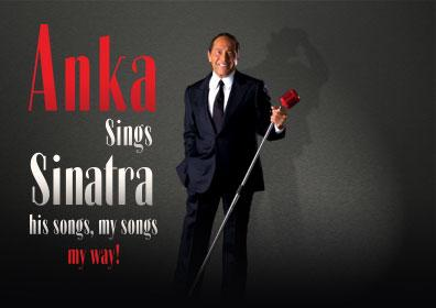 Paul Anka posing with a mic