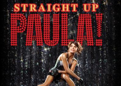 Paula Abdul posing next to Straight Up Paula! sign