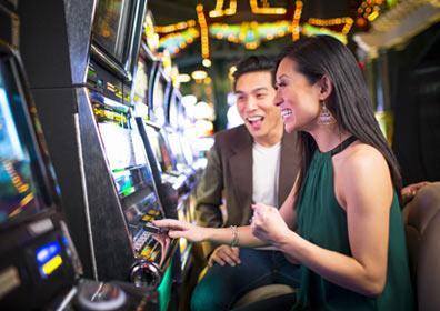 People enjoying slot machines in the casino.