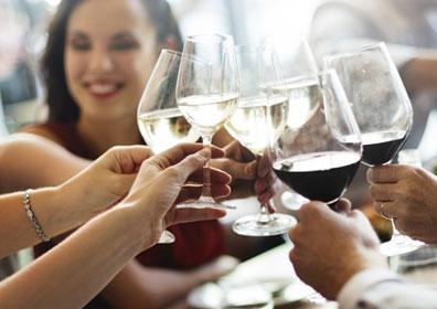 A group of people toasting with wine at a dinner