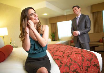 Woman sitting on bed putting in her earring in Suite. Husband in the background adjusting his suit.