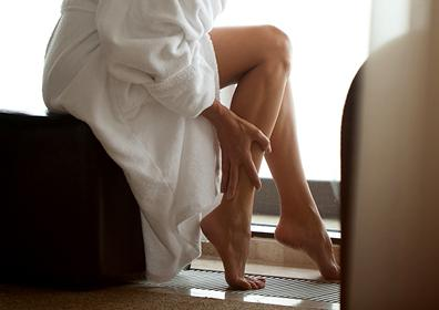 A woman in a robe touching her newly waxed legs