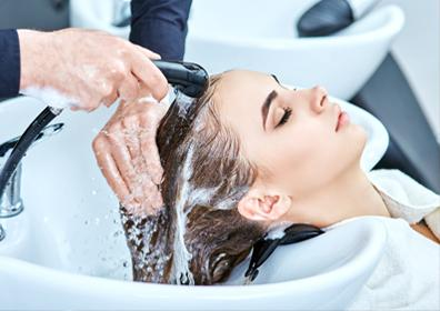 Woman getting shampoo washed out of her hair