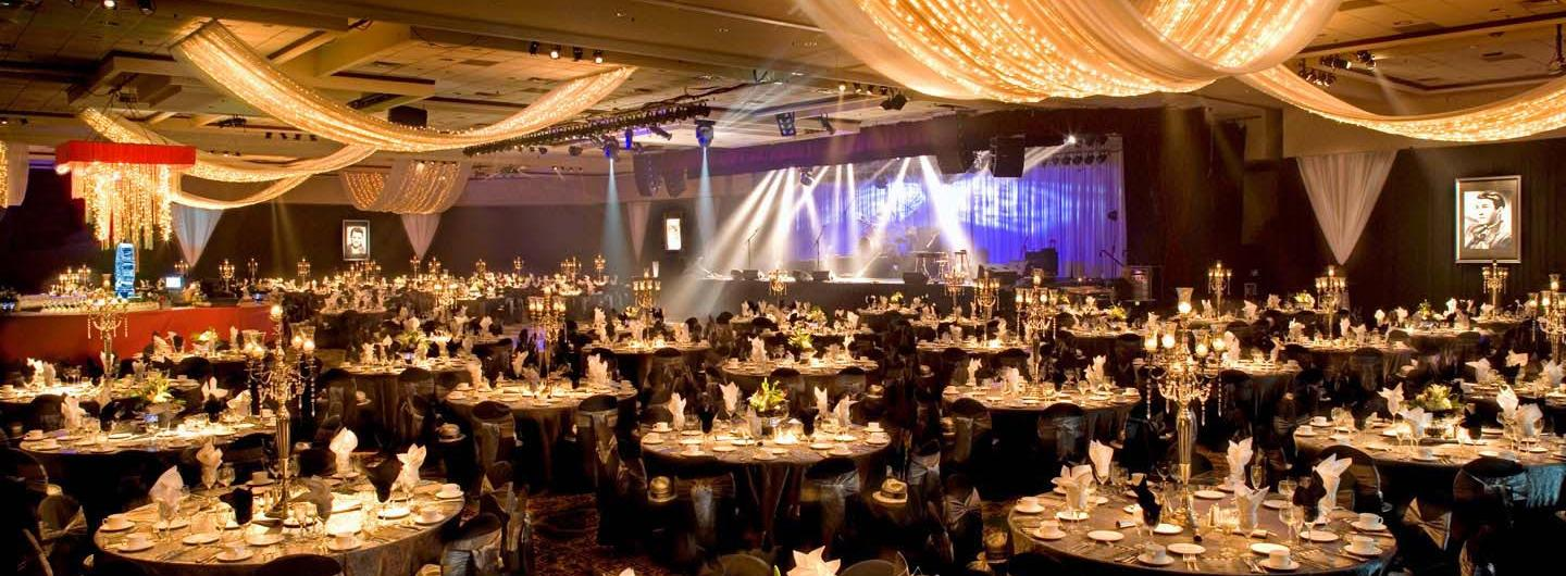 Beautiful Shot of Decorated Silver Legacy Convention Space with Gold Lighting and Stage Lit up with Blue Lights