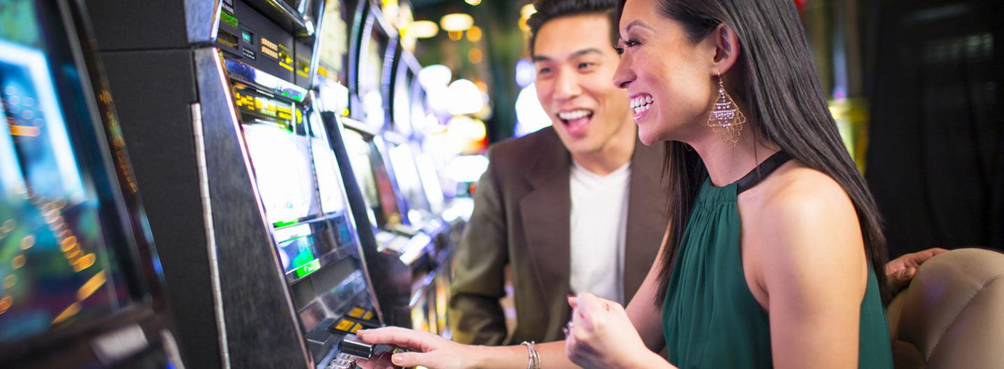 People enjoying slot machines in the casino.