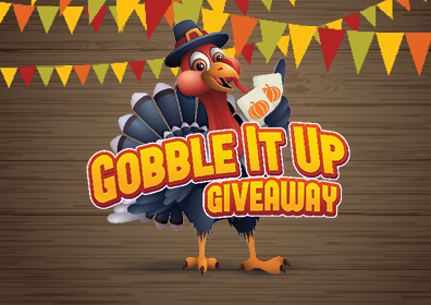 Graphic design image featuring a black and red turkey centered with a black and red pilgrim hat on and holding two white cards with small orange pumpkins on each card in his left hand. In front of the turkey are the words Gobble it Up Giveaway in yellow outlined in red. Behind the turkey is a brown wood plank background with green, yellow, and orange triangle banners at the top of image.