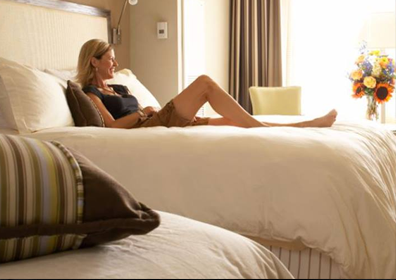 A women laying on a hotel bed for the Capri Hotel Package