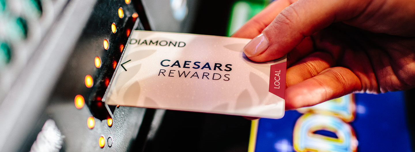 Caesars Rewards Local Diamond card being inserted into a slot machine
