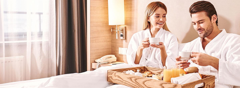 Two people enjoying breakfast in bed