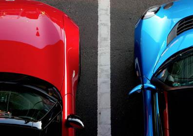 Aerial picture of a red car and a blue car in a parking lot
