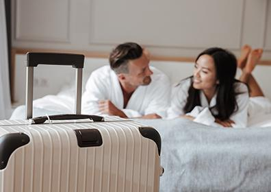 A happy couple smiling on their hotel room bed in white robes with a suitcase in view