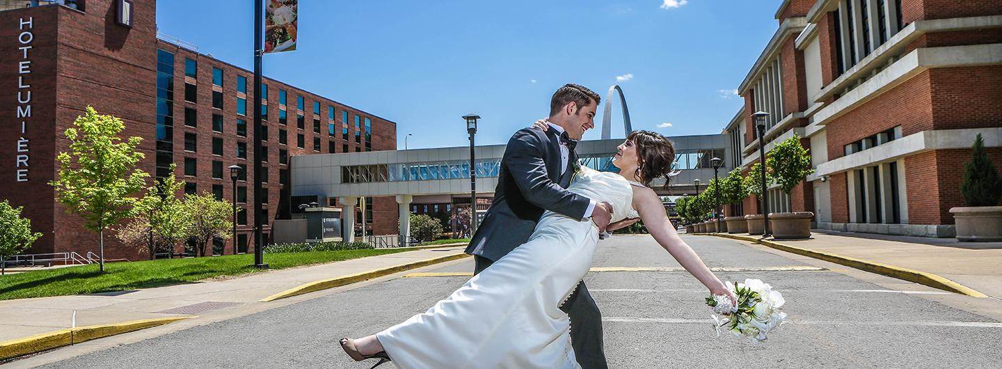 Bride and Groom in front of Hotel Lumiere and the St. Louis Arch in background