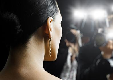 A Woman's Face in Profile with a Long Earring Gets Her Picture Taken by Different Cameras with Flashes On