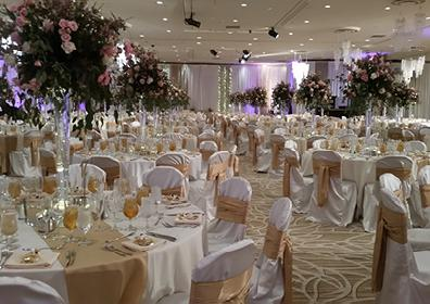 A Large White and Gold Room Full of Tables and Chairs all Covered with Various Drinks