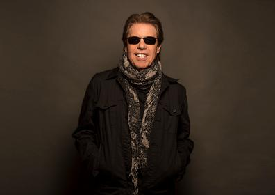 man standing up wearing a jacket and scarf with sunglasses on