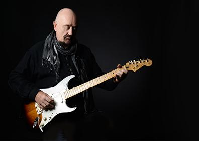 man playing a white guitar